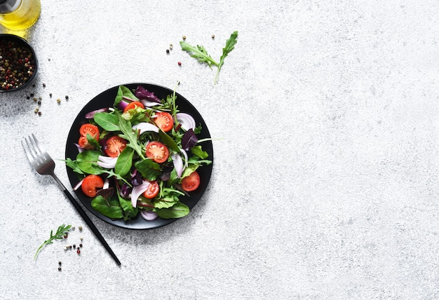 Meng de salade met tomaten, uien en olijfolie in een zwarte plaat.