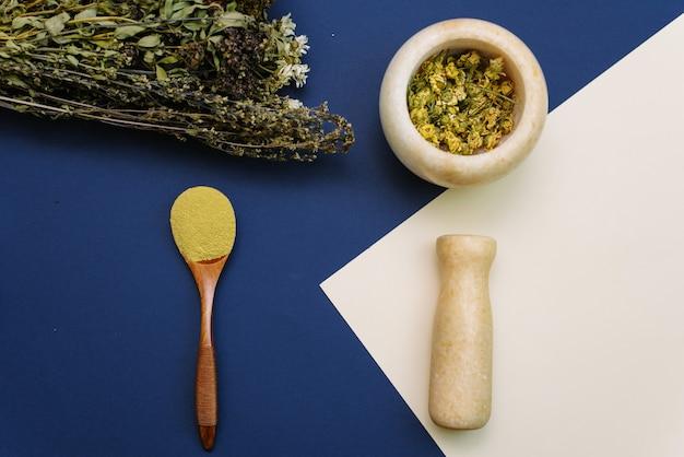 Meng gedroogde bloemen in een marmeren vijzel om cosmetica en scrub te maken om het gezicht te reinigen
