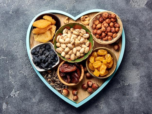 Meng gedroogde vruchten en noten op een grijze ondergrond. bovenaanzicht van superfoods.
