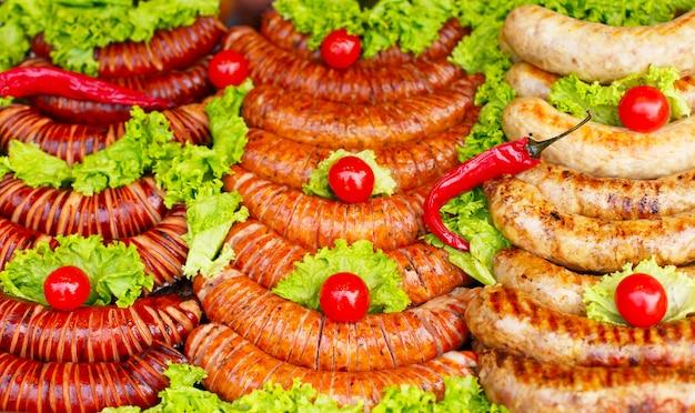 Meng gegrilde worstjes op pan met kruiden, tomaat en specerijen, buiten.
