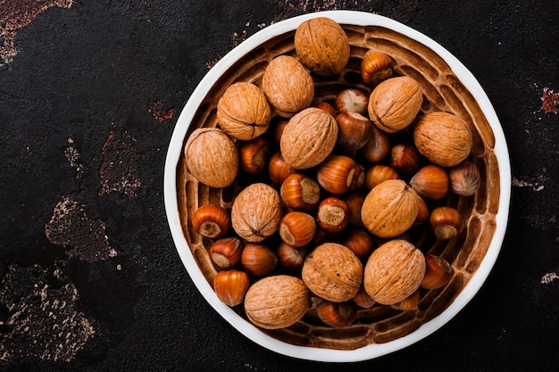 Meng gezonde rauwe hazelnoten en walnoten in een keramische plaat op een bruin betonnen oppervlak.