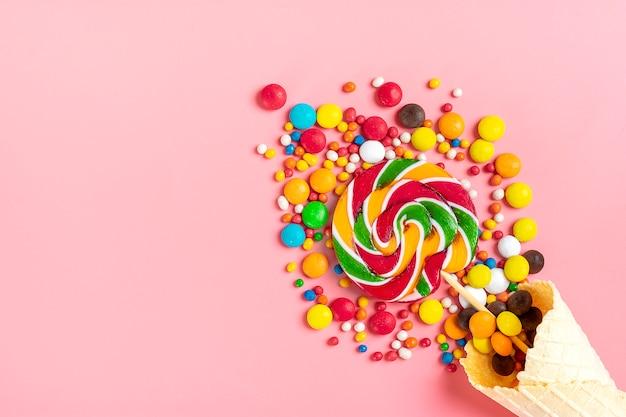 Meng kleurrijke chocoladesnoepjes gemorst uit ijswafelkegel op roze. plat leggen