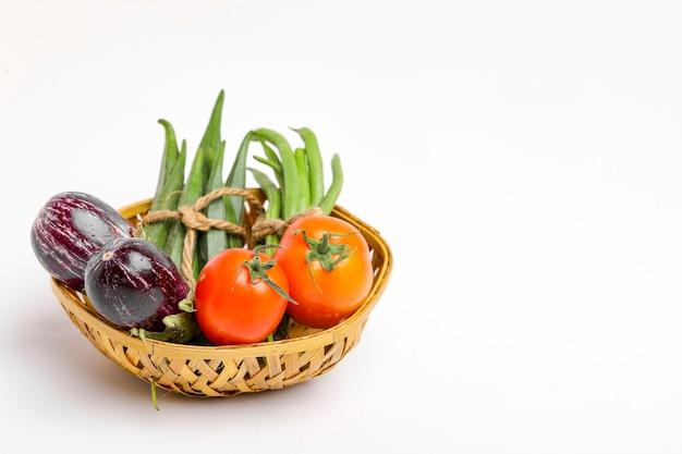 Meng rauwe groente in houten kom op witte achtergrond