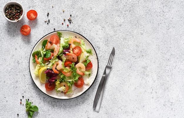 Meng salade met tomaten en gegrilde garnalen met saus en clematis op de keukentafel. uitzicht van boven. concrete voedselachtergrond.