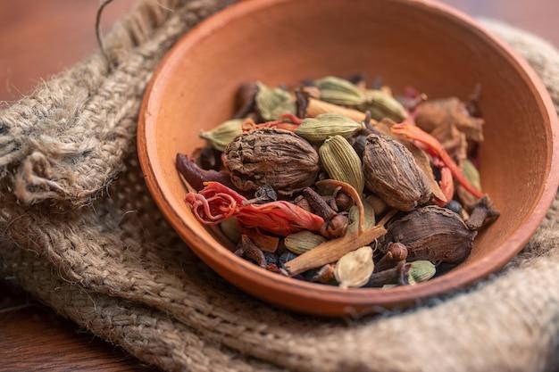 Meng specerijen en kruiden in een aarden kom op een stoffen zak, indiase specerijen, voedsel en keukeningrediënten