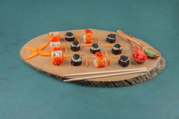 Meng sushi en lepels ingemaakte gember en wasabi op een houten bord.