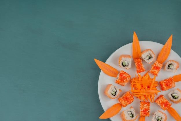 Meng sushi met plakjes wortel op een houten bord.