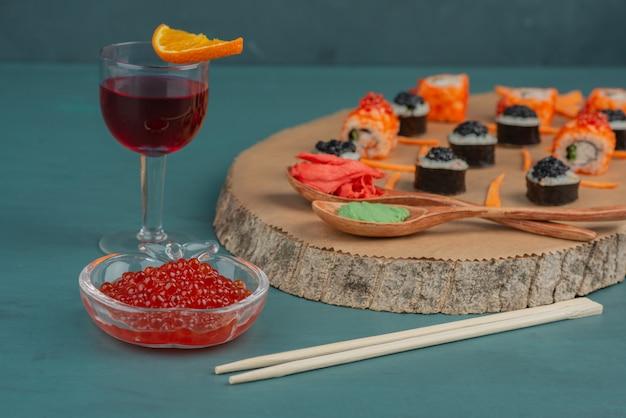 Meng sushi, rode kaviaar en een glas rode wijn op blauwe tafel.