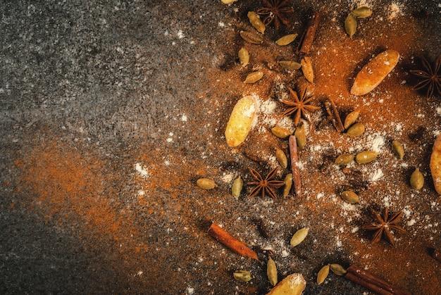 Mengsel van gedroogde gemalen spionnen voor hete pittige thee of indiase masala chai kaneel, anijs, kardemom, gember, op een witte marmeren tafel - chili, paprika, curry, kurkuma, gember. copyspace bovenaanzicht