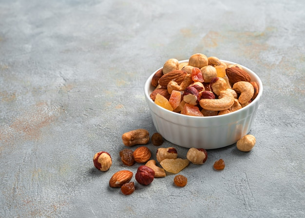 Mengsel van gedroogde vruchten en verschillende soorten noten in een witte kom op grijze marmeren achtergrond