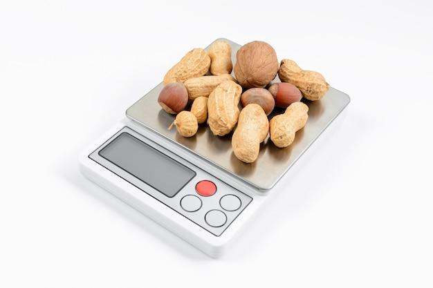 Mengsel van noten op elektronische weegschaal met witte achtergrond. dieet en gewichtsverlies concept.