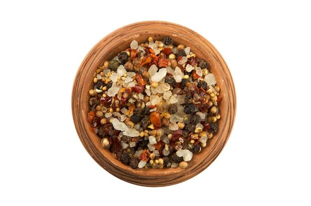 Mengsels van paprika en zout in een glanzende kop geïsoleerd op een witte achtergrond
