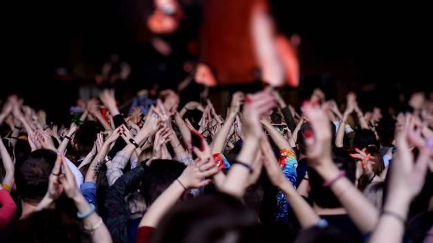 Menigte bij concert - juichende menigte in heldere kleurrijke podiumverlichting. publiek op openluchtmuziekfestival