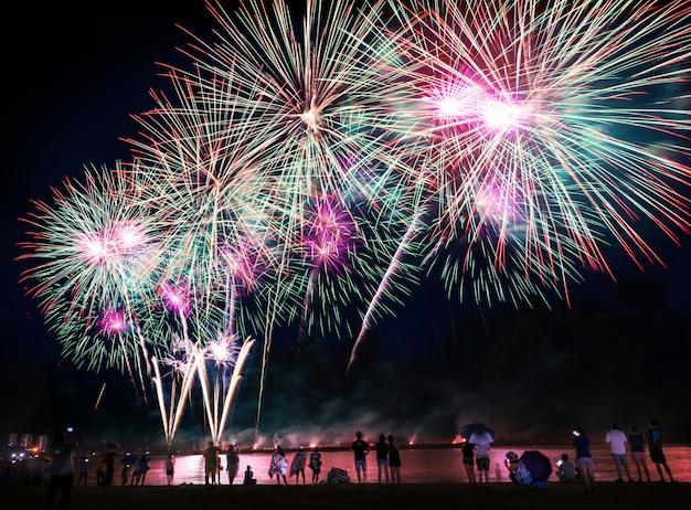 Menigte kijken naar vuurwerk op het strand
