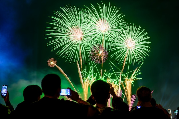 Menigte kijkt naar vuurwerk en viert opgerichte stad. groen toonlicht.