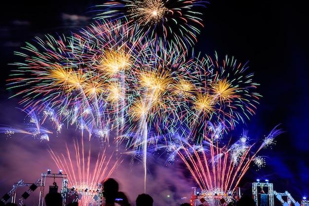 Menigte kijkt naar vuurwerk en viert opgerichte stad. mooi kleurrijk vuurwerkvertoning in stedelijk voor viering op donkere nacht