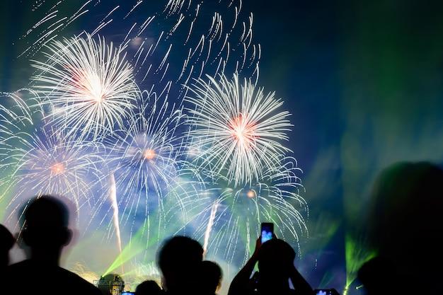 Menigte kijkt naar vuurwerk en viert opgerichte stad. mooi kleurrijk vuurwerkvertoning in stedelijk voor viering op donkere nacht.