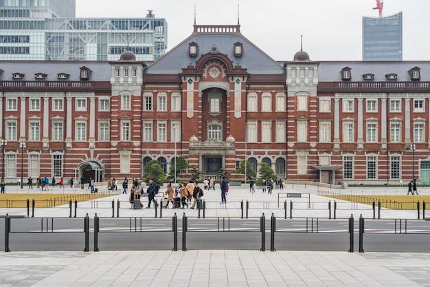 Menigte onbekende mensen die een bezoek brengen aan en genieten van tokyo station en marunouchi met autoverkeer tokyo