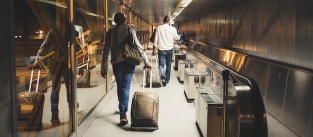 Menigte van mannen en vrouwen binnen de luchthavenpoort die naar start gaat of net is aangekomen. mensen lopen met handtas en koffers en trolley met wielen. reizigers over de hele wereld-concept