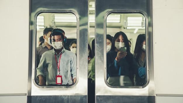 Menigte van mensen die een gezichtsmasker dragen op een drukke openbare metro