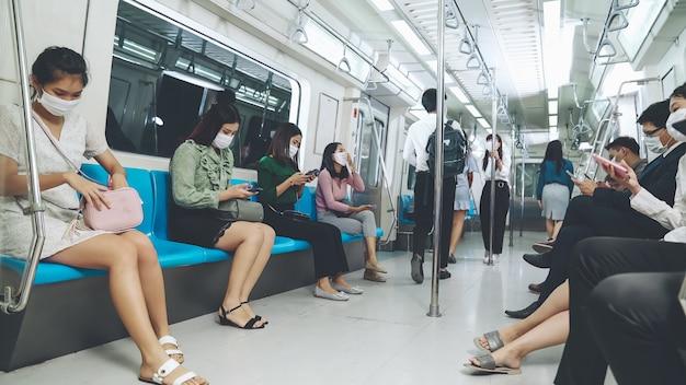 Menigte van mensen die een gezichtsmasker dragen op een drukke openbare metrotreinreis