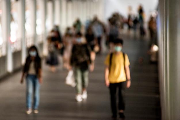 Menigte van mensen die maskers dragen die in het nieuwe normaal lopen