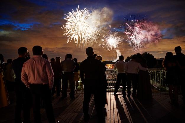 Menigte van mensen kijken naar vuurwerk in de avondlucht