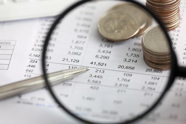 Mening bij financiële details in lijst door vergrootglasclose-up
