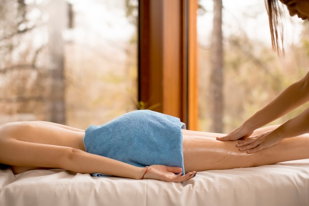 Mening bij mooie blonde vrouw die van een massage geniet in het kuuroord