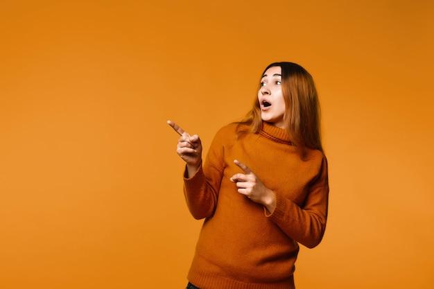 Mening die van mooie verraste roodharige kaukasische vrouw gekleed in trui, iets met vingers op de linkerhoek toont