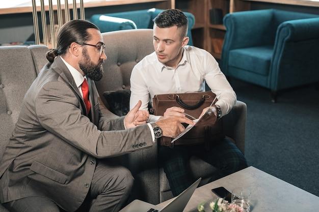 Mening geven. bebaarde donkerharige zakenpartner die zijn mening geeft over de situatie die met jonge man spreekt