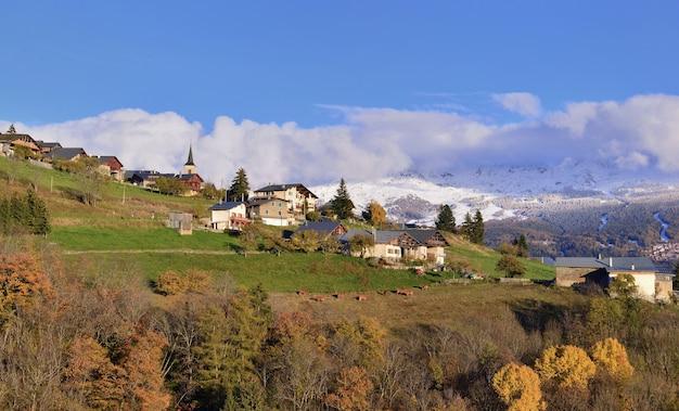 Mening over alpien dorp op een heuvel en een besneeuwde bergachtergrond