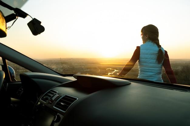 Mening van binnenuit van een jonge vrouw die zich dichtbij haar auto bevindt die van warme zonsondergang geniet. meisjesreiziger die op voertuigkap leunen die avondhorizon bekijken.