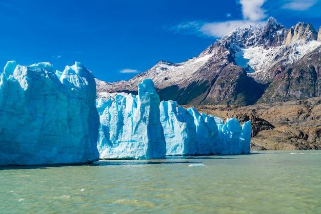 Mening van blauwe ijsberg van gray glacier in gray lake en mooie sneeuwberg bij het nationale park van torres del paine op zuidelijk chileens het ijsgebied van patagonië.
