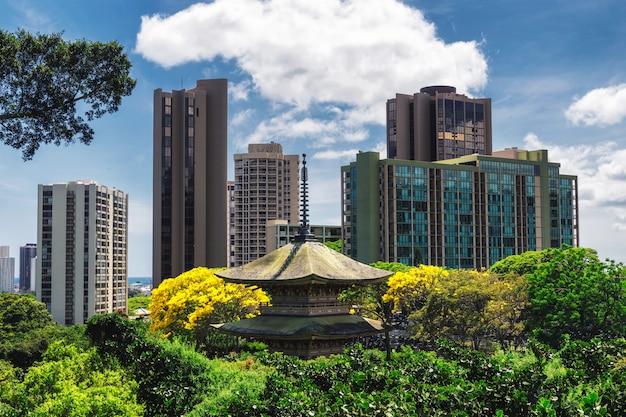 Mening van chinese pagode in het herdenkingspark van honolulu en bureaugebouwen op een zonnige dag, hawaï