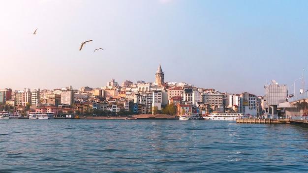 Mening van cityscape van istanboel galata-toren met drijvende toeristenboten in bosphorus, istanboel turkije