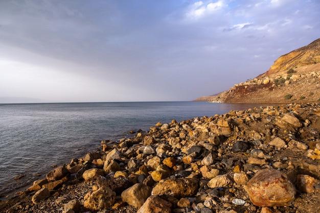Mening van de kustlijn van de dode zee bij zonsondergang in jordanië. zoutkristallen bij zonsondergang