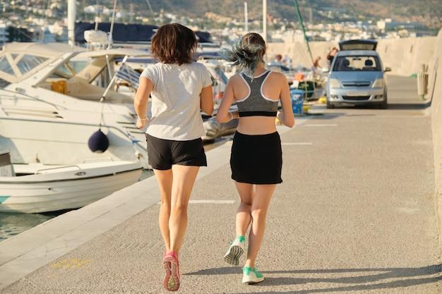 Mening van de rug van moeder en dochter die bij kustpromenade lopen