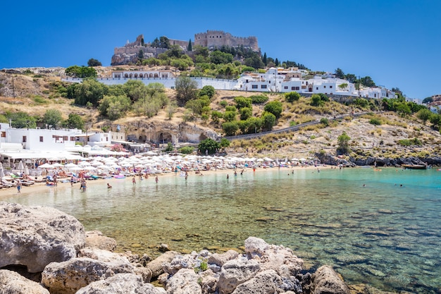 Mening van de strandmier de vesting in stad lindos. rhodos, griekenland