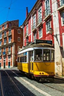 Mening van de uitstekende beroemde gele elektrotrams die nog vandaag in lissabon, portugal in omloop brengen.