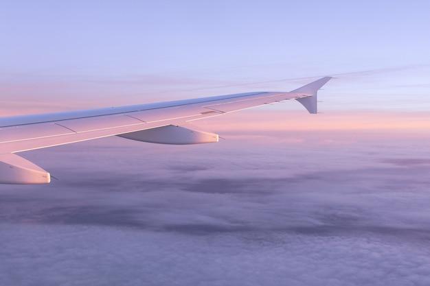 Mening van de vliegtuigpatrijspoort op de hemel van roze kleur met luchtwolken en de vleugel van het vliegtuig