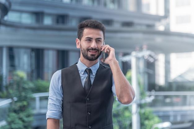 Mening van een jonge aantrekkelijke bedrijfsmens die smartphone gebruiken