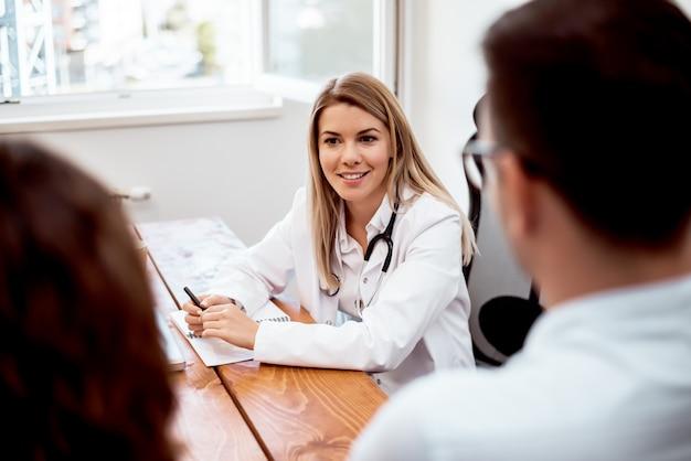 Mening van een jonge aantrekkelijke vrouwelijke arts die een jong paar patiënten adviseert.