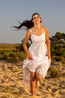 Mening van een mooi jong meisje met een lange witte kleding die op zand loopt.