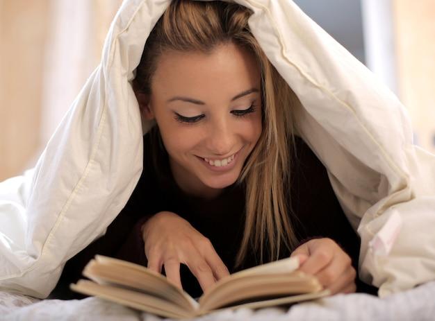 Mening van een mooi kaukasisch wijfje dat een boek leest onder een witte deken