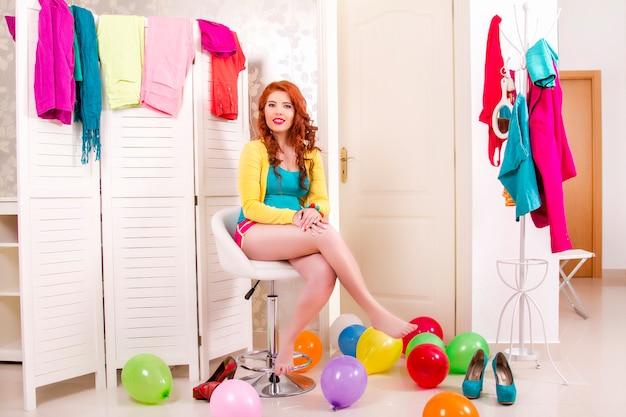 Mening van een mooi roodharigemeisje in haar kleurrijke slaapkamer.