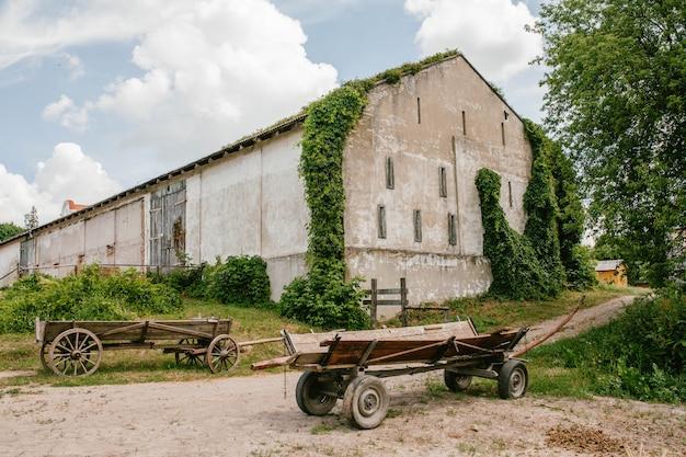 Mening van een oud gebouw in klimop en houten karren
