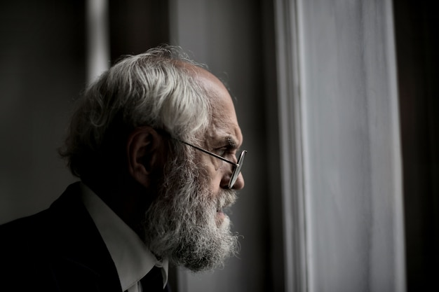 Mening van een oud kaukasisch mannetje dat uit het venster kijkt
