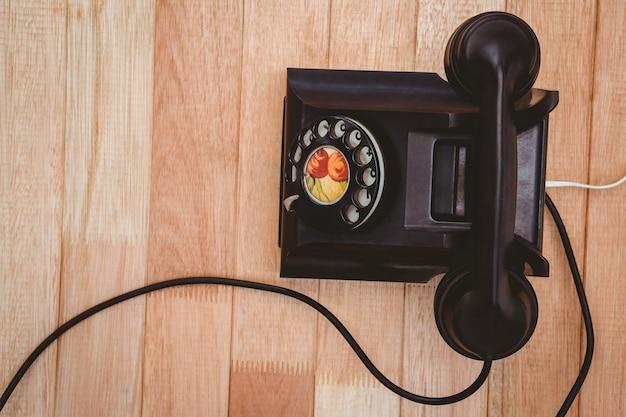 Mening van een oude telefoon op houten bureau