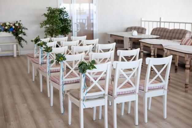 Mening van een scène van de huwelijksceremonie in een ruimte met verscheidene rijen witte stoelen en samenstellingen van verschillende bloemen